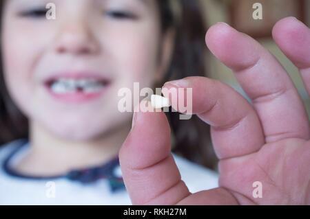 Poco più di 5 anni ragazza mostrando il suo primo bambino dente caduto fuori. Primo piano. Foto Stock