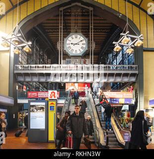 Amburgo, Germania - Mar 20, 2018: pendolari su escalator sotto il grande orologio interno Amburgo stazione ferroviaria centrale Foto Stock