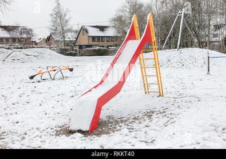 Parco giochi per bambini in una scuola materna per i bambini in inverno con neve - Diapositiva. Foto Stock