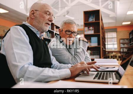 Vista laterale di due uomini anziani lavorando sul computer portatile seduti in classe. Alti uomini seduti in una libreria e l apprendimento dei propri corsi su un laptop.