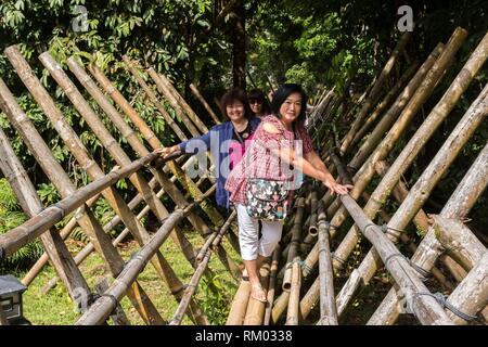 Le donne con cautela a piedi attraverso un ponte di bambù nella giungla a Sarawak Villaggio Culturale, il Damai, Sarawak, Malaysia. Foto Stock