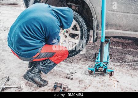 Il processo di lavoro di rimozione delle ruote dalla macchina sulla strada in inverno. Sostituzione di pneumatici invernali per l'estate. Foto Stock