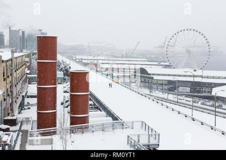 Seattle, Washington: una solitaria giovane passeggiate lungo il chiuso Alaskan modo viadotto come una forte tempesta di neve ricopre la città in sei pollici di neve. La hi Foto Stock