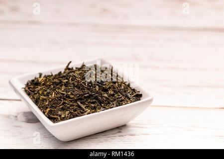 Vista ravvicinata di secco di menta marocchina foglie di tè con in bianco piccola piastra in ceramica sul tavolo bianco Foto Stock