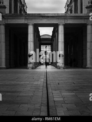 Un uomo cammina attraverso un tunnel ostentate circondato dalla straordinaria architettura in bianco e nero Foto Stock