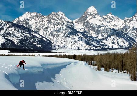 Un audace giovane maschio snowboarder vele off di un ripiano di neve incontaminata in vista dell'incredibile Teton gamma della montagna nel Parco Nazionale di Grand Teton vicino a Jackson Hole, Wyoming negli Stati Uniti. Foto Stock