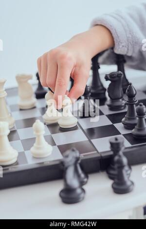 Ritagliare la mano del bambino tenendo la figura sulla scacchiera su sfondo grigio Foto Stock