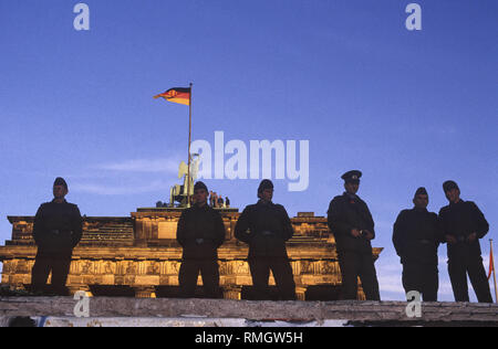 Migliaia di oriente e occidente i berlinesi celebrare l'apertura della frontiera sul muro di Berlino alla Porta di Brandeburgo. GDR guardie di frontiera di impedire alle persone di entrare nella zona soggetta a restrizioni nella piazza davanti alla Porta di Brandeburgo e il Pariser Platz. Foto Stock