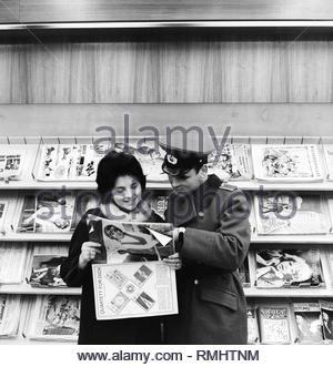 Un soldato dell'esercito popolare nazionale (NVA) sta con la sua fidanzata in un edicola a Berlino, ex capitale della Repubblica democratica tedesca, la Repubblica democratica tedesca. Foto Stock