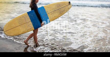 Giovane e attraente felice surfer girl nella bellissima spiaggia che trasportano il giallo della tavola da surf passeggiate nell'oceano godendo le vacanze estive a Isola tropicale Foto Stock