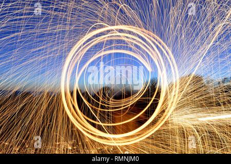 La lana di acciaio fotografia. Sentieri di luce creato da scintille durante una lunga esposizione fotografia di masterizzazione di lana di acciaio. Foto Stock