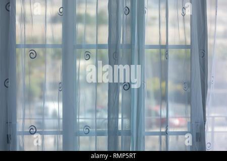 Tende a rete nella parte anteriore della finestra patio con la luce del sole sulle macchine parcheggiate dietro Foto Stock