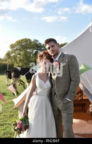Un bel paio di sposarsi in un romantico Farm Ubicazione - lei è una rossa e wers un breve vintage abiti da sposa. Egli è alto e ha tatuaggi Foto Stock