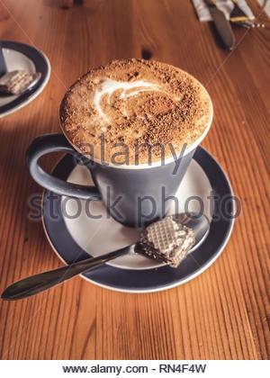 Chai Latte in grigio di una tazza ceramica con biscotto di wafer Foto Stock