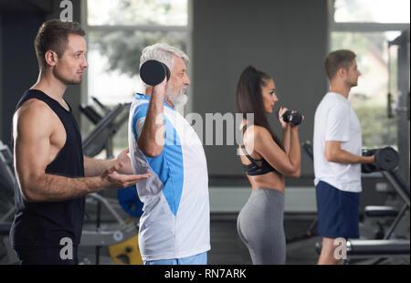 Vista laterale di persone che lavorano in una palestra moderna. Le donne e gli uomini utilizzando speciali attrezzature sportive. Trainer professionale aiutando, supporto di vecchio uomo facendo esercizi. Uomo anziano il sollevamento pesi. Foto Stock