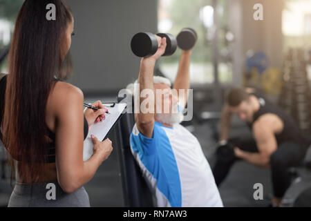 Professional personal trainer lavora con clienti in palestra, osservando con cartella e penna, iscritto. Uomo anziano con i capelli grigi seduta, tenendo le mani in alto e facendo esercizi con pesi. Foto Stock