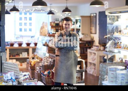 Ritratto del maschio sorridente Proprietario del negozio delicatessen indossando il grembiule Foto Stock