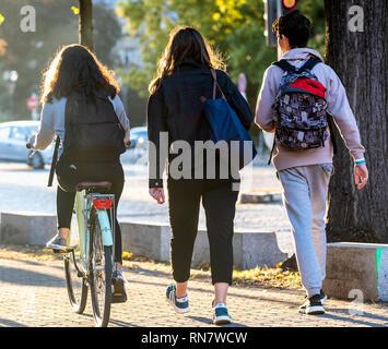 Strasburgo, Alsazia, Francia, Europa, vista posteriore di 2 adolescenti a piedi e una ragazza in bicicletta sul marciapiede, Foto Stock