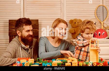 Il padre e la madre con bambino gioca costruttore. infanzia felice. Cura e sviluppo. La famiglia felice e giorno. Ragazzino con papà e mamma Foto Stock
