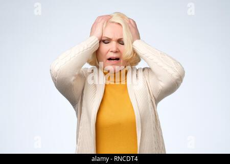 Triste senior vecchia donna che guarda verso il basso e pianto Foto Stock