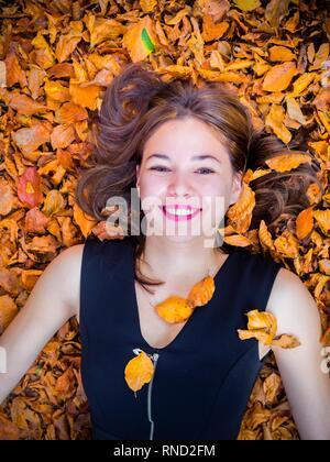 Bella ragazza teen sta sorridendo alla vista della macchina fotografica direttamente da sopra sdraiato sulla schiena ridacchiando gioous divertimento Foto Stock