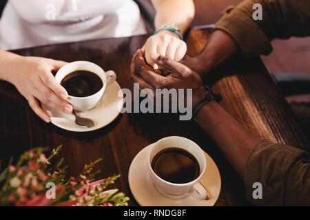 Giovane su di una data seduta a un coffee shop tabella. Close up man mano di contenimento di una donna su una tabella con tazze di caffè dal lato.