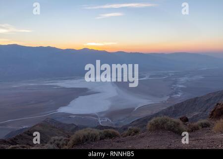 Il tramonto visto oltre Death Valley (Badwater) verso il Panamint Range. Vista da Dante, vista parco nazionale della Valle della Morte, California, Stati Uniti. Foto Stock