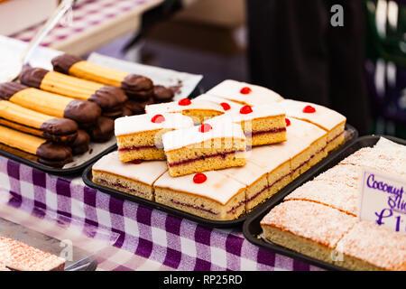 Dolci e biscotti nella vetrina del negozio con i cartellini dei prezzi. Deliziosi dolci sulla vendita. Concetto di cibo con la vendita di pasticceria Foto Stock