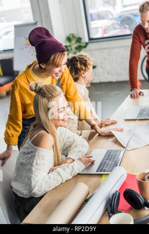 Messa a fuoco selettiva dei gruppo di maschi e femmine di progettisti che lavorano su progetti di avvio con i laptop e blueprint in ufficio loft Foto Stock