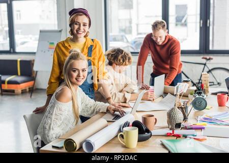 Gruppo di maschi e femmine di progettisti che lavorano su progetti di avvio con i laptop e blueprint in ufficio loft Foto Stock