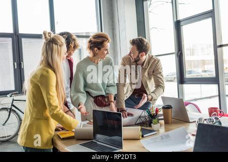 Gruppo di sorridere maschi e femmine di architetti che lavorano sul progetto alla scrivania con computer portatili in ufficio loft Foto Stock