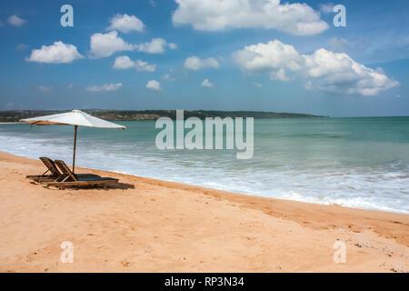 Lettino rilassante sedie con ombrellone sulla spiaggia di sabbia bianca guardando verso l'oceano su Bali Indonesia Foto Stock