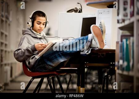 Ragazzo adolescente seduto con i piedi e la lettura di un libro con le cuffie in una libreria.