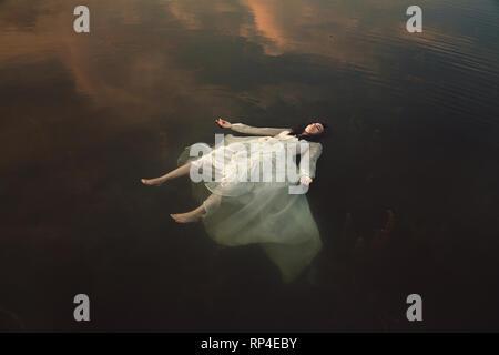 Ragazza innocente dormire in acque scure Foto Stock