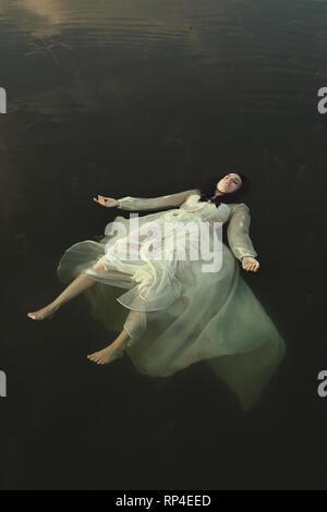 Donna galleggianti in verde le acque del lago Foto Stock