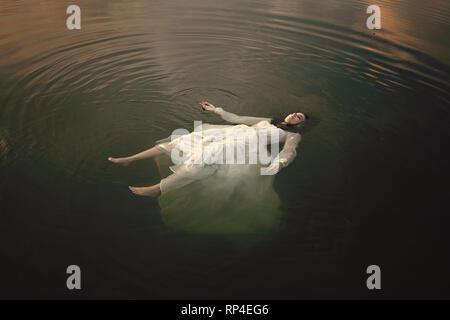 Giovane donna che giace morto nelle acque del lago Foto Stock