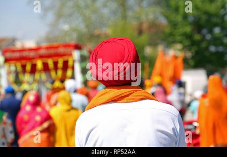 Indian uomo con turbante rosso e camicia bianca durante una parata riligous Foto Stock