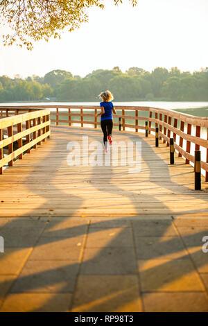 Foto dal retro della donna sportiva in esecuzione sul ponte di legno in estate. Foto Stock