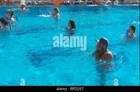 e7d22d672614 Femmina di aerobica in acqua di gruppo e formatore maschio fare ...