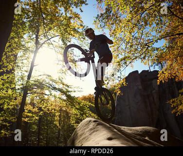 Sihlouette del professionista sportivo ciclista permanente sulla ruota posteriore in prova bicicletta, giovane pilota acrobatico rendendo trucco sul bordo di boulder nella foresta sulla giornata di sole. Concetto di sport estremi Foto Stock
