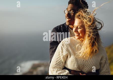Coppia romantica godendo della reciproca compagnia sulla loro vacanza. Uomo che abbraccia la sua donna da dietro e sia godendo la vista. Foto Stock