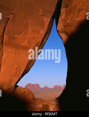 Stati Uniti d'America, Arizona, il parco tribale Navajo, distante buttes della Monument Valley sono visualizzati tramite lacrima Arch, una apertura in una parete di pietra arenaria. Foto Stock