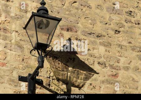Il vecchio stile nero lampada getta un' ombra su un muro di mattoni,Knaresborough,North Yorkshire, Inghilterra. Foto Stock