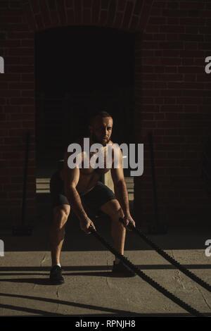 Atletica Giovane con corda di battaglia facendo esercizio di allenamento funzionale palestra fitness. Corda aiuta a coinvolgere tutti i gruppi muscolari allo stesso tempo, mentre ens Foto Stock