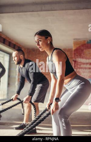 Montare caucasico giovane esercitando con battaglia corde in palestra. Donna e uomo vestito in abiti sportivi formazione insieme facendo combattendo la corda allenamento, con p Foto Stock