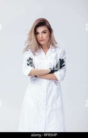 Ritratto di giovane donna professional cosmetologo in guanti neri. Donna estetista medico in studio