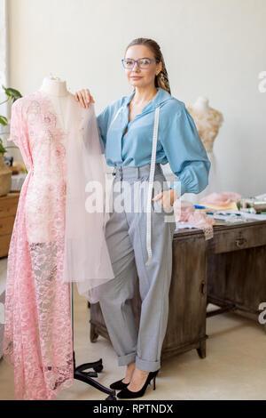 Femmina creativo sarta indossando occhiali, vestito in Elegante camicetta e pantaloni dritti con nastro di misurazione sorridente piacevolmente lavora con fantoccio Foto Stock