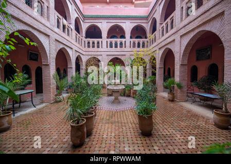 Cortile interno con pareti in piastrelle e pavimento di mosaico. Tradizionale e ornati arabesque colorate sculture di parete al di sopra di un arco nel riad marocchino