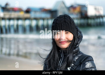 Una donna cinese che indossa una giacca invernale nel vento che soffia ad Old Orchard Beach Maine in una giornata di sole. Foto Stock
