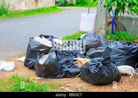 Pila garbage nero su strada e di gocce di pioggia sul sacco in città con lo spazio di copia consente di aggiungere del testo Foto Stock